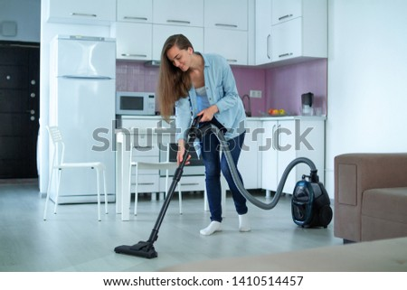 Woman cleaning house using vacuum cleaner. Household chores and housekeeping  #1410514457