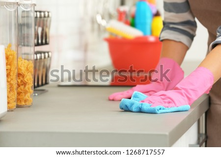 Woman cleaning kitchen counter with rag, closeup
