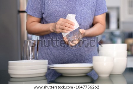 Woman Cleaning product concept wiping dishware cleaner in home and kitchen