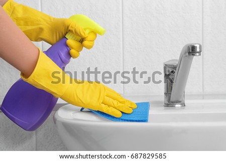 Woman cleaning sink with sponge cloth and detergent in bathroom #687829585
