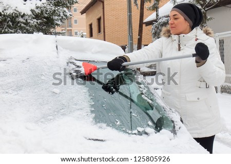 Woman cleaning snow from the car