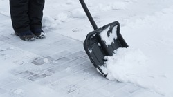 Woman cleaning snow with shovel outdoors on winter day, closeup