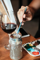 Woman cleaning the brush while painting a canvas on a wooden easel, next to the color palette and a glass of wine.