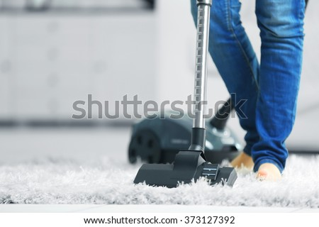 Woman cleaning the carpet with vacuum cleaner in the living room - Shutterstock ID 373127392