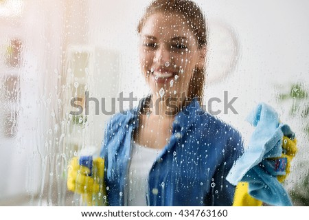 Woman cleaning window with special cleaner