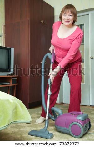 Woman cleaning with vacuum cleaner in living room