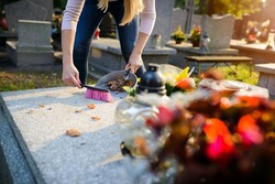 Woman cleans a grave. November 1 All Saints' Day