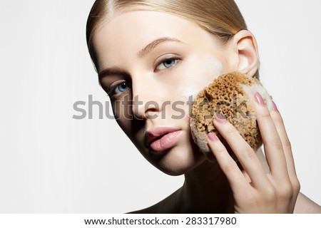 Woman cleans and exfoliates the skin with a natural sponge foam face on a white background