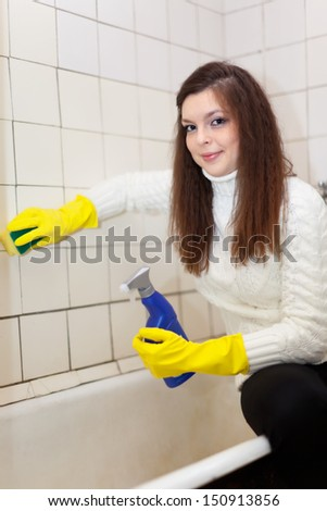 woman cleans bathroom with sponge at her home