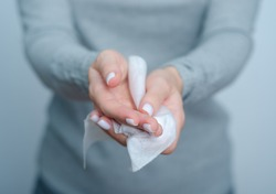 Woman cleans hands wet antibacterial wipe on gray background