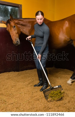 Woman cleans horse box by horse fork, vertical format