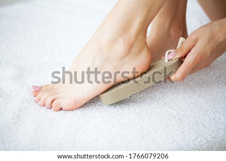 Woman cleans the heel of the foot with pumice Stockfoto ©