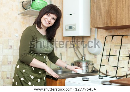 woman cleans the kitchen sink with melamine sponge