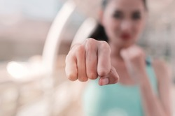 Woman clenched fist ready to punch close up with copy space. workout for martial art boxing, self defense.