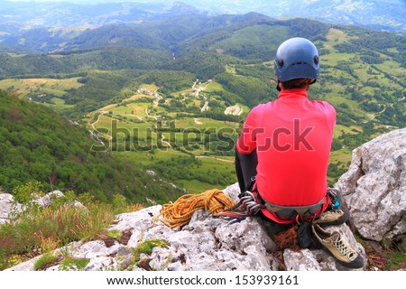 Woman climber resting after finishing the route and admiring the view