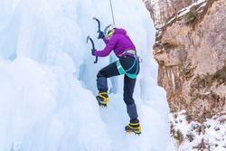 Woman climbing down the side of an icy slope, hanging on a rope attached to her harness