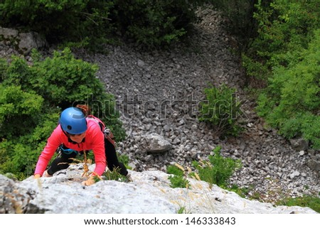 Woman climbing on the rock route, high above ground