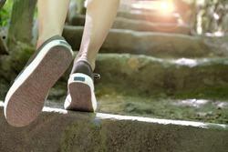 woman climbing stone steps to success