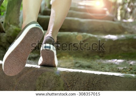 woman climbing stone steps to success