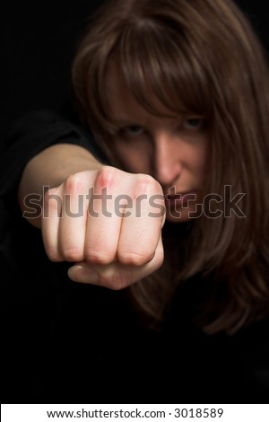 woman close up portrait pointing fist on black backdrop