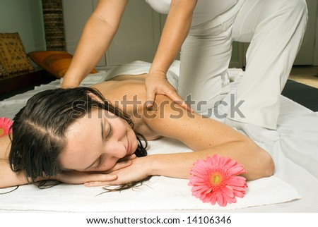 Woman closes her eyes and relaxes as she gets a  massage. Horizontally framed photograph. - stock photo