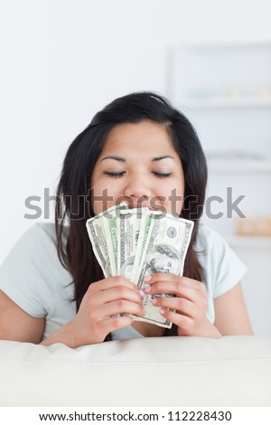 Woman closing her eyes as she holds some dollar bills in a living room