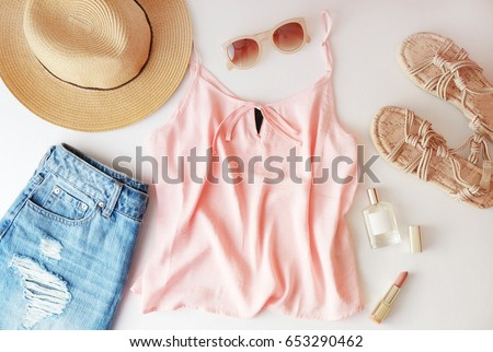 Woman clothes and accessories: pink top, jeans skirt, perfume, sandals, sunglasses, hat, lipstick on white background. Flat lay trendy fashion feminine background. Fashion beauty background.