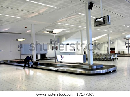 Woman collect bag from luggage Carousel at Adelaide Airport
