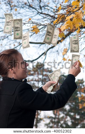 woman collecting dollar notes hanging from autumn tree