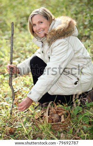 Woman collecting mushrooms in the forest