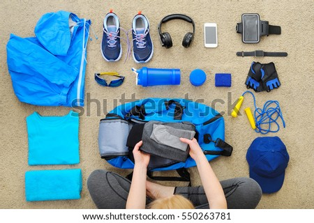 Woman collects a sports bag for sports. Fitness and a healthy lifestyle. #550263781