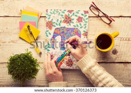 Shutterstock Woman coloring an adult coloring book, new stress relieving trend, mindfulness concept, hand detail