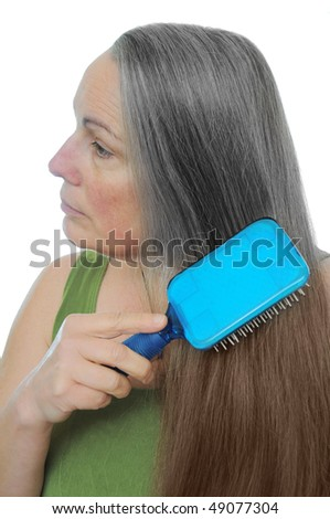 Woman combs her hair gray to brown showing the signs of old age and youth