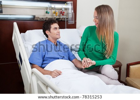 Woman comforting male patient at hospital