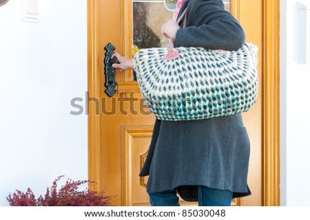 Woman coming home with her groceries and standing at the front door