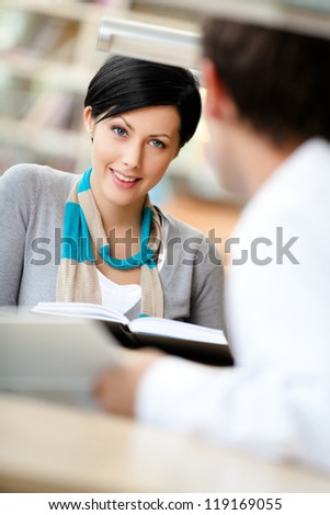 Woman communicates with man showing her something in the book sitting at the desk at the reading hall