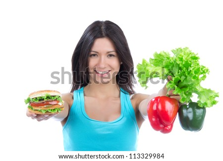 Woman comparing tasty fast food unhealthy burger or hamburger and healthy fresh peppers and salad isolated on a white background