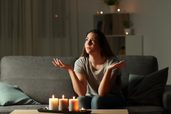 Woman complaining during a blackout sitting on a couch in the living room at home