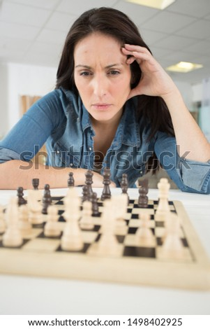 woman concentrating on her next chess move