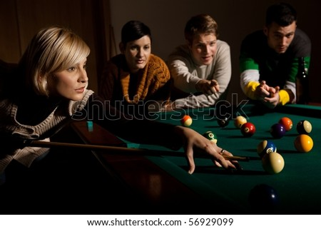 Woman concentrating on snooker game, leaning on table, aiming at ball, holding cue, friends watching in background.?