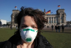 Woman concerned of corona virus wearing a medical mask in front of Reichstag building, Berlin Germany