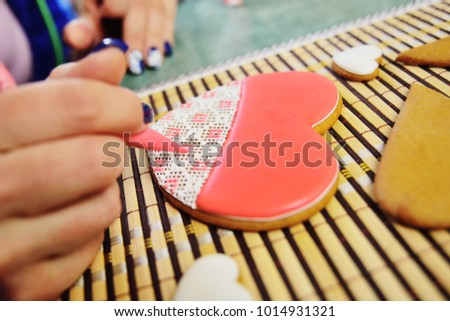 woman confectioner decorates and decorates the glaze with gingerbread cookies in the shape of heart. Valentine's Day, February 14, symbol, valentine, gift. #1014931321