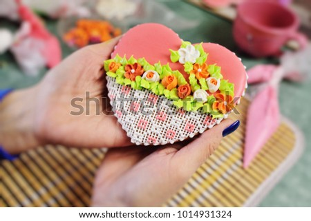 woman confectioner decorates and decorates the glaze with gingerbread cookies in the shape of heart. Valentine's Day, February 14, symbol, valentine, gift. #1014931324