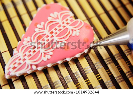 woman confectioner decorates and decorates the glaze with gingerbread cookies in the shape of heart. Valentine's Day, February 14, symbol, valentine, gift. #1014932644