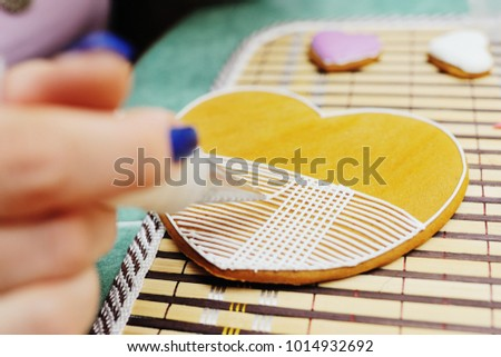 woman confectioner decorates and decorates the glaze with gingerbread cookies in the shape of heart. Valentine's Day, February 14, symbol, valentine, gift. #1014932692