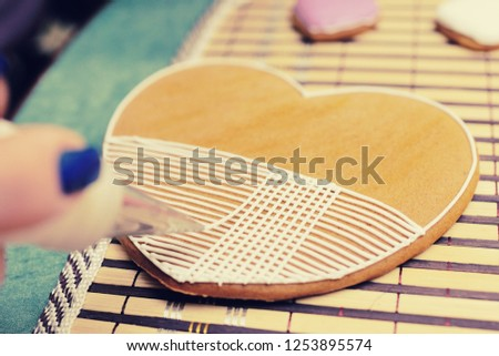 woman confectioner decorates and decorates the glaze with gingerbread cookies in the shape of heart. Valentine's Day, February 14, symbol, valentine, gift. #1253895574