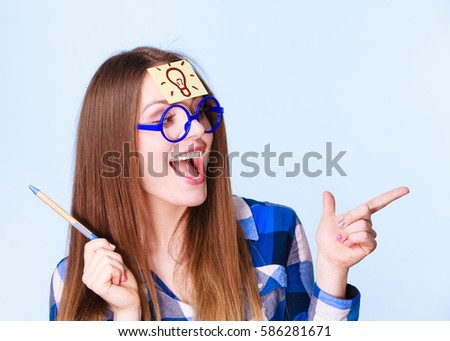 Woman confused thinking seeks a solution, paper card with light idea bulb on her head. Excited girl with many ideas celebrates success. Eureka creativity concept studio shot on blue. - Shutterstock ID 586281671