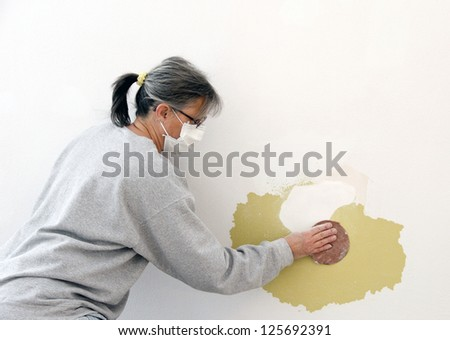 woman construction worker wearing a mask is sanding a patch on a wall
