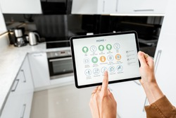 Woman controlling kitchen appliances with a digital tablet, close-up on mobile device with launched smart home application. Smart home concept