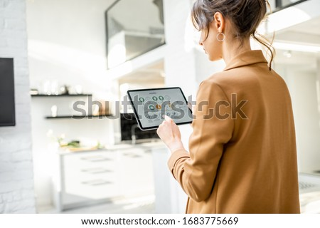 Woman controlling smart home devices using a digital tablet with launched application in the white living room. Smart home concept